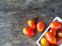 Tomate-cerise rouge délicieuse, cuvette blanche, trois morceaux dehors, fond en bois Images libres de droits