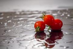 Tomate-cerise sur un fond noir avec de l'eau Images stock