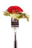 Tomate con la ensalada en una fork Imágenes de archivo libres de regalías