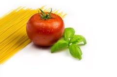 Tomate con las pastas de la albahaca y de los espaguetis foto de archivo