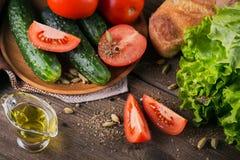 Tomate, concombre, laitue, baguette, huile d'olive et épices photos libres de droits