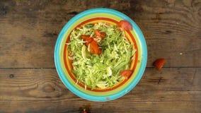 Tomate cortado de queda no prato com salada, movimento lento video estoque