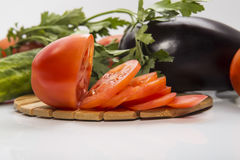Tomate coupée en tranches se trouvant sur le conseil près d'autres légumes Image stock