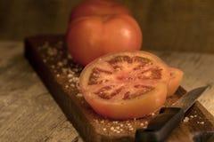 Tomate coupée en tranches sur un conseil en bois Photos libres de droits