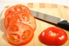 Tomate coupée en tranches sur un panneau de découpage photo libre de droits