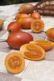 Tomate de árbol fresco. Algunos tomates de árbol sobre una mesa de jardín unos partidos por la mitad y otros enteros Stock Photos