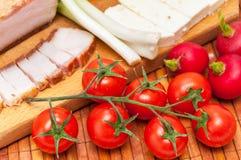 Tomate de cereja com bacon, as cebolas verdes, o queijo e os rabanetes Fotografia de Stock