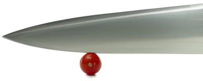 Tomate de cereja e grande faca Fotografia de Stock Royalty Free