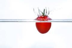 Tomate de cereja que cai na água com um respingo Fotografia de Stock