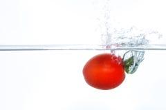 Tomate de cereja que cai na água com um respingo Fotos de Stock