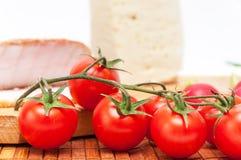 Tomate de cereza con tocino y queso en fondo Imagen de archivo