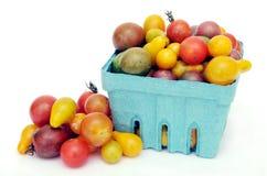 Tomate de cereza dentro y fuera de la cesta Imágenes de archivo libres de regalías