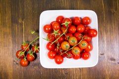 Tomate de cereza en la placa cuadrada en la madera desde arriba Fotografía de archivo libre de regalías