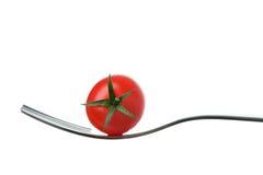 Tomate de cereza en una fork contra blanco Imágenes de archivo libres de regalías