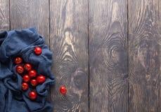 Tomate de cereza jugoso fresco en toalla azul en la tabla de cocina imagen de archivo