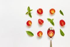 Tomate de cereza rojo, hojas verdes de la albahaca y cuchara en el fondo blanco fotografía de archivo