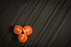 Tomate de cereza y pastas negras crudas fotos de archivo libres de regalías