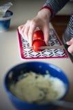 Tomate de coupe de main Photos libres de droits