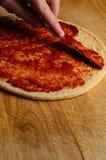Tomate de extensión de la mano en base de la pizza Foto de archivo libre de regalías