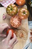 Tomate de frottage de chef sur une tranche de pain Photos stock