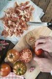 Tomate de frottage de chef sur une tranche de pain Images libres de droits