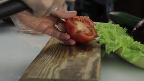 Tomate del corte de la mujer en una tabla de cocina cortar verduras en una tabla de cortar de madera almacen de metraje de vídeo
