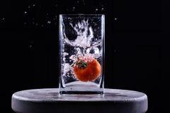 Tomate, die in Wasser fällt Lizenzfreies Stockfoto