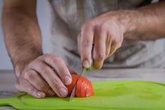 Tomate do corte na placa de corte verde Imagem de Stock Royalty Free