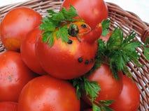 Tomate drôle dans un panier en osier et des feuilles de persil Photographie stock libre de droits