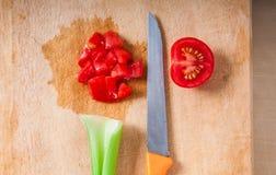 Tomate e aipo cortados de cereja na placa de corte Imagens de Stock Royalty Free