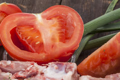Tomate e carne frescos em uma superfície de madeira Foto de Stock Royalty Free