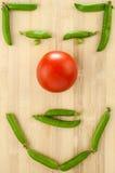 Tomate e ervilhas verdes apresentados em uma tabela Imagens de Stock Royalty Free