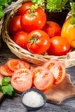 Tomate e hierbas frescos en una cesta Imagen de archivo