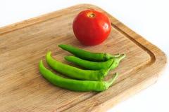 Tomate e pimentas na placa de desbastamento Foto de Stock