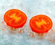 Tomate eingefroren im Eis Stockbilder