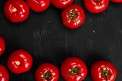 Tomate em um fundo preto com gotas realísticas da reflexão e da água Tomates frescos Fotos de Stock