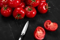 Tomate em um fundo preto com gotas realísticas da reflexão e da água Tomates frescos Foto de Stock Royalty Free