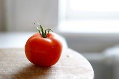 Tomate em uma placa de madeira do corte no fundo branco Copie o espa?o Tomate fresco wased cozinhando Tomate com gotas de foto de stock