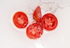 Tomate en agua en el fondo blanco Imagenes de archivo