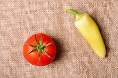 Tomate et poivre sur le fond de toile à sac Images stock