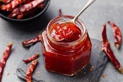 Tomate et sauce chili, confiture, confiserie dans un pot en verre sur un fond en pierre gris Photos stock