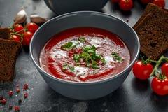 Tomate et soupe fraîche à basilic avec l'ail, grains criqués de papper, servis avec de la crème et le pain de levain Photos stock