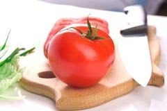 Tomate fraîche mûre rouge sur le panneau de découpage avec le couteau images stock