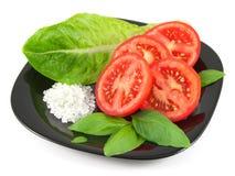 Tomate fresco cortado con las hojas de la albahaca, la hoja de la ensalada y la sal del mar en la placa negra Fotografía de archivo