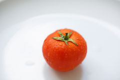 Tomate mûre d'un plat blanc Photo stock
