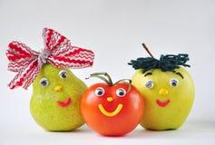 Tomate, manzana y pera divertidos en un fondo blanco Fotos de archivo