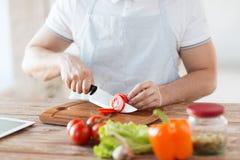 Tomate masculino do corte da mão a bordo com faca Imagens de Stock