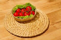 Tomate med sallad på en korg Arkivfoto