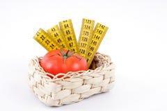 Tomate mit einem messenden Band Stockbilder
