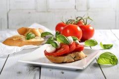 Tomate, mozzarella, madeira do bruschetta da manjericão na tabela Fotos de Stock Royalty Free